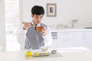 朝食を食べる男子高校生の写真素材 [FYI01919308]