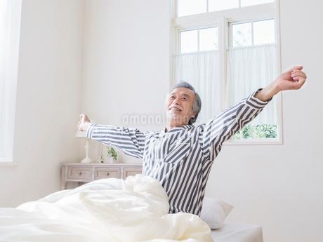 ベッドで背伸びをするシニア男性の写真素材 [FYI01919326]