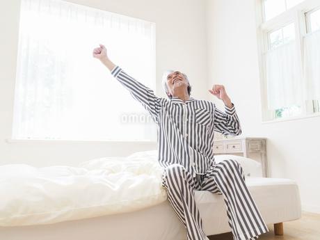 ベッドで背伸びをするシニア男性の写真素材 [FYI01919483]