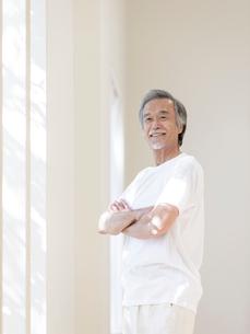 窓辺で腕を組むシニア男性の写真素材 [FYI01919699]