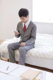 スマートフォンを操作する男子高校生の写真素材 [FYI01919758]