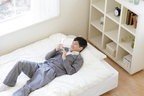 スマートフォンを操作する男子高校生の写真素材 [FYI01919998]