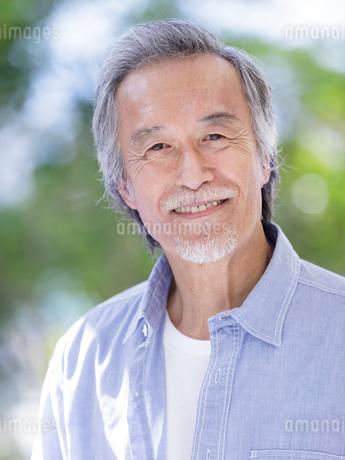 庭先で微笑むシニア男性の写真素材 [FYI01920002]