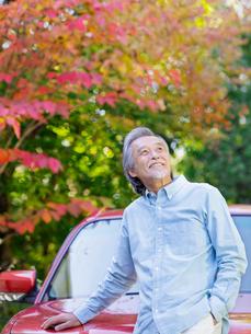 車にもたれて見上げるシニア男性の写真素材 [FYI01920039]