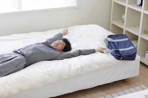 ベッドに寝る男子高校生の写真素材 [FYI01920041]
