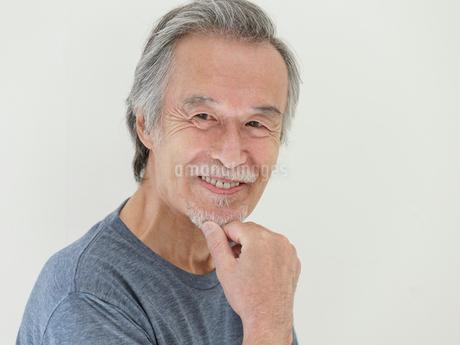 顎に手を当てた笑顔のシニア男性の写真素材 [FYI01920052]