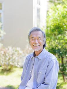 庭先で微笑むシニア男性の写真素材 [FYI01920115]