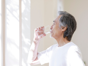窓辺で水を飲むシニア男性の写真素材 [FYI01920121]