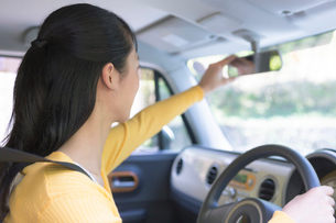 自動車のバックミラーを調節する女性の写真素材 [FYI01920138]
