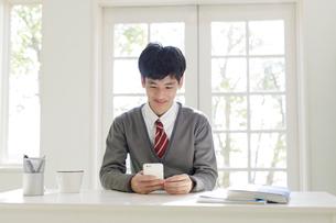 スマートフォンを操作する男子高校生の写真素材 [FYI01920191]