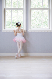 窓辺に立つバレリーナの女の子の写真素材 [FYI01920342]