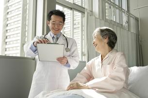 介護ベッドの女性患者と男性医師の写真素材 [FYI01922056]