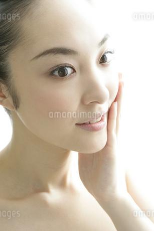 顔に手をあてる若い女性のビューティーイメージの写真素材 [FYI01924139]