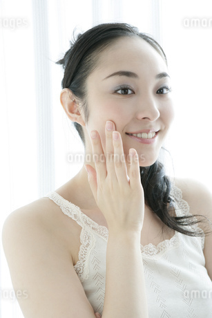 顔に手をあてる若い女性のビューティーイメージの写真素材 [FYI01924261]