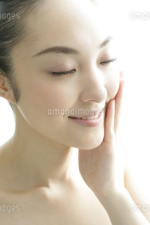 顔に手をあてる若い女性のビューティーイメージの写真素材 [FYI01924509]