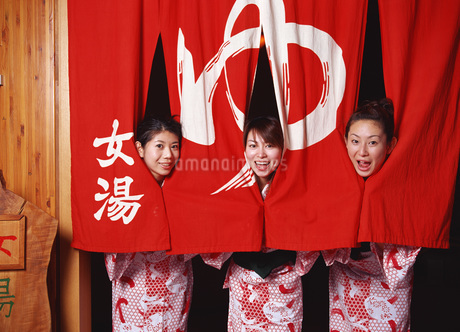 のれんに包まれる浴衣姿の女性達の写真素材 [FYI01926138]