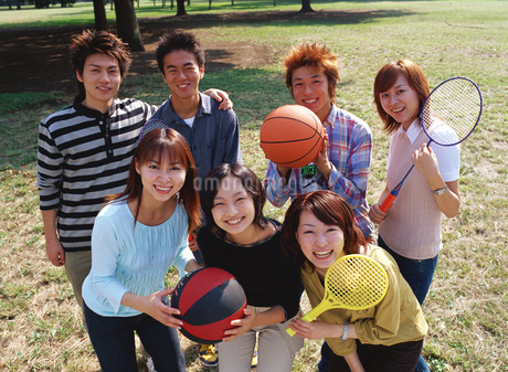 公園でラケットやボールを持って並ぶ男女の写真素材 [FYI01926176]