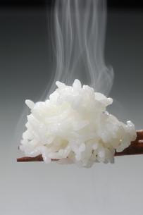 箸にのせた湯気のたつごはんの写真素材 [FYI01928260]