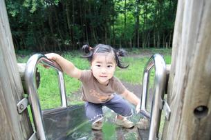 公園の遊具で遊ぶ女の子の写真素材 [FYI01928273]
