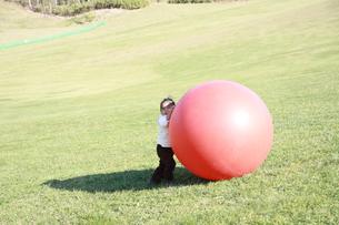 芝生でボール遊びをする女の子の写真素材 [FYI01928432]