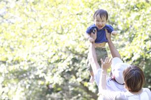 新緑の公園で父親に高い高いされる男の赤ちゃんの写真素材 [FYI01929748]