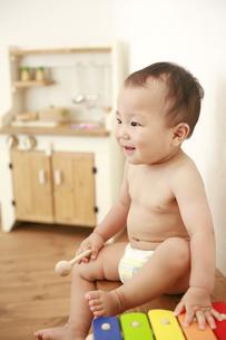 椅子に座っている裸の男の赤ちゃんの写真素材 [FYI01929781]