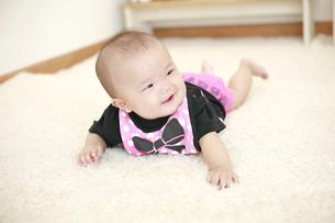 うつ伏せで寝転がる女の赤ちゃんの写真素材 [FYI01929867]