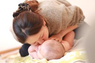 赤ちゃんにキスをする母親の写真素材 [FYI01929891]