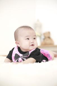 うつ伏せで寝転がる女の赤ちゃんの写真素材 [FYI01929898]