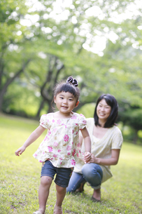 新緑の公園で走る女の子の写真素材 [FYI01929934]
