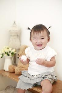 ベンチに座る笑顔の女の赤ちゃんの写真素材 [FYI01929982]