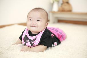 うつ伏せで寝転がる女の赤ちゃんの写真素材 [FYI01930073]