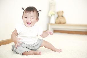 お座りをする笑顔の女の赤ちゃんの写真素材 [FYI01930677]