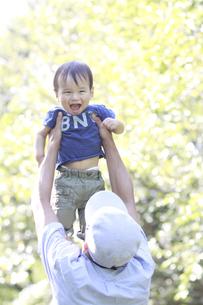 新緑の公園で父親に高い高いされる男の赤ちゃんの写真素材 [FYI01931292]