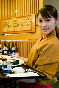 料理を運ぶ女性店員の写真素材 [FYI01931976]