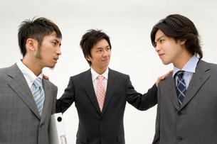仲裁に入る男性と睨みあう男性2人の写真素材 [FYI01932416]