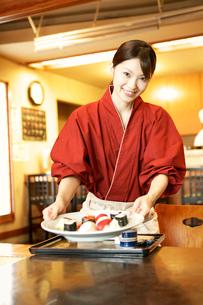 寿司を運ぶ女性店員の写真素材 [FYI01933187]