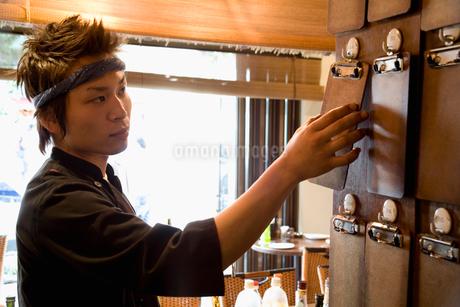 壁に伝票ホルダーを掛ける男性店員の写真素材 [FYI01933334]
