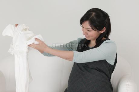 産着をたたむ妊婦の写真素材 [FYI01934021]