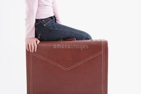 カバンの上に座る女性の写真素材 [FYI01934647]