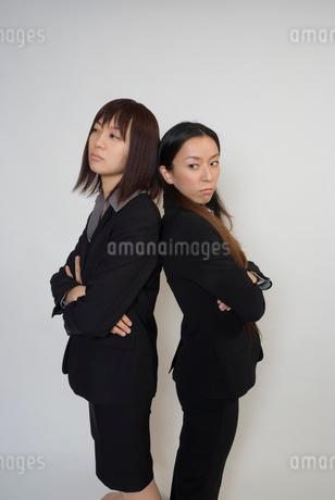 背を向けてけん制するスーツ姿の女性の写真素材 [FYI01936438]