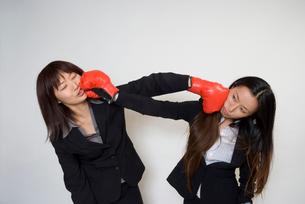ボクシンググロ-ブで殴りあうスーツの女性の写真素材 [FYI01936451]