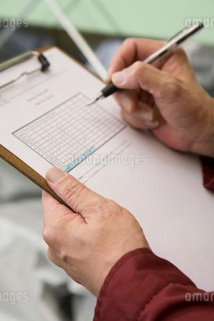 紙に書き込む中年男性の写真素材 [FYI01936476]