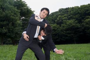 外で取っ組み合うスーツ姿の男性の写真素材 [FYI01936609]