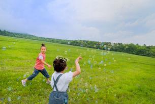 シャボン玉を追いかける少女たちの写真素材 [FYI01937012]
