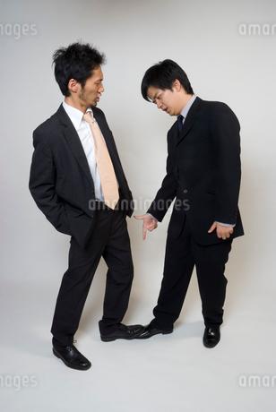 足を踏んで争いあうスーツ姿の男性の写真素材 [FYI01937183]