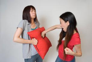 クッションの上からお腹を殴る女性の写真素材 [FYI01939392]