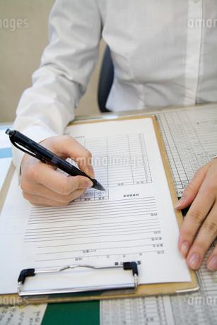 書類に書き込む若い女性の写真素材 [FYI01939539]
