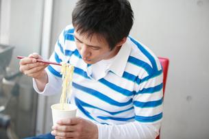カップ麺を食べる男性の写真素材 [FYI01940225]