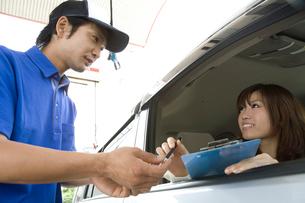 女性客にボールペンを渡すガソリンスタンドの男性店員の写真素材 [FYI01940584]